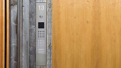 Metallene Türstation, eingelassen in die Holzfassade einer modernen Villa.
