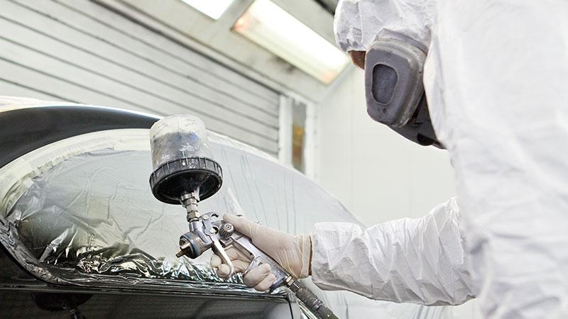Mitarbeiter eines Hamburger Autolackierbetriebs in Overall, mit Atemschutzmaske und Farbspritzpistole lackiert Auto.