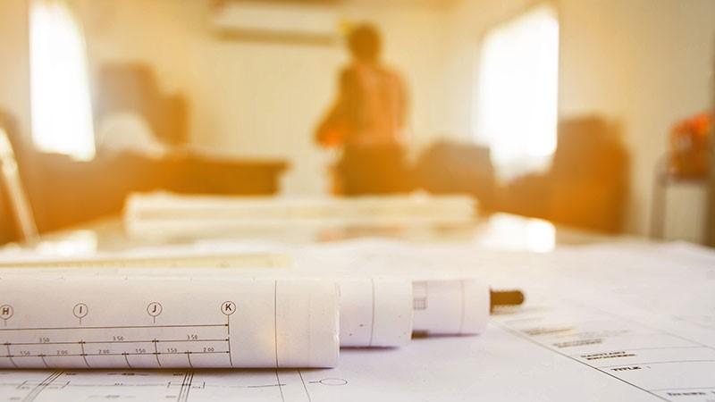 Gebäudeenergiegesetz: Bauzeichnungen auf Tisch in mobilem Planungsbüro.