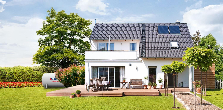 Sonnenkollektoren auf einem Hausdach, daneben ein PRIMAGAS Flüssiggas-Tank auf einer Rasenfläche.