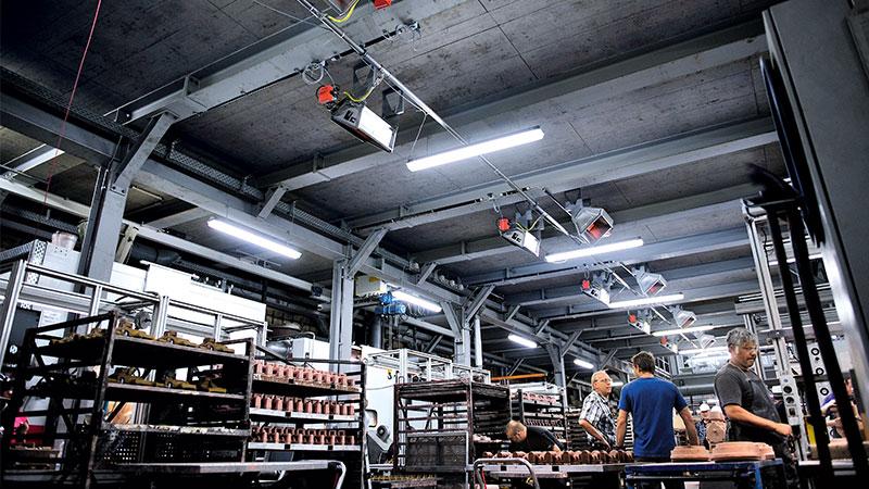 Arbeiter in Fertigungshalle, Fokus auf Hallenheizungen (Hellstrahler) unter der Decke.