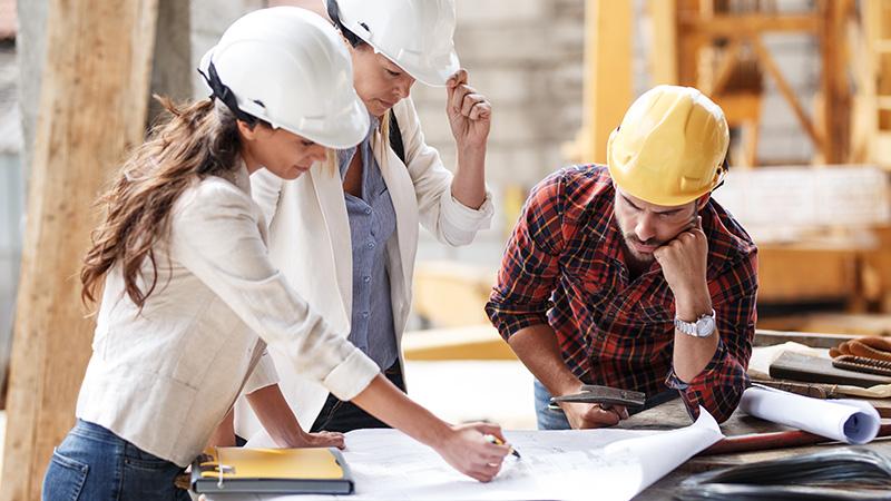 Zwei weibliche und ein männlicher Architekt mit Bauzeichnung bei der Objektleitung.