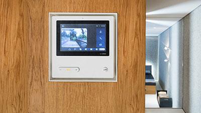 Innenbereich einer modernen Villa. Im Vordergrund ein Video-Panel, eingelassen in eine Holzverkleidung.