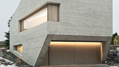 Wohngebäude in monolithischer Bauweise aus Beton mit metallener Eingangsfront.
