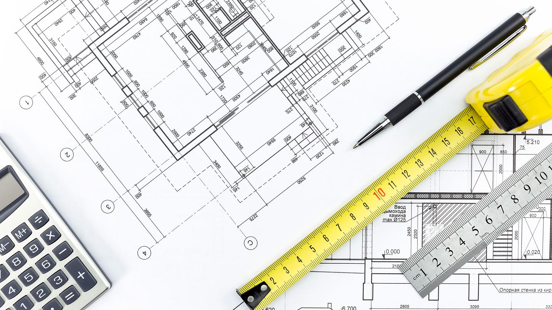 Maßband und Druckbleistift auf Skizze von Gebäudegrundriss.