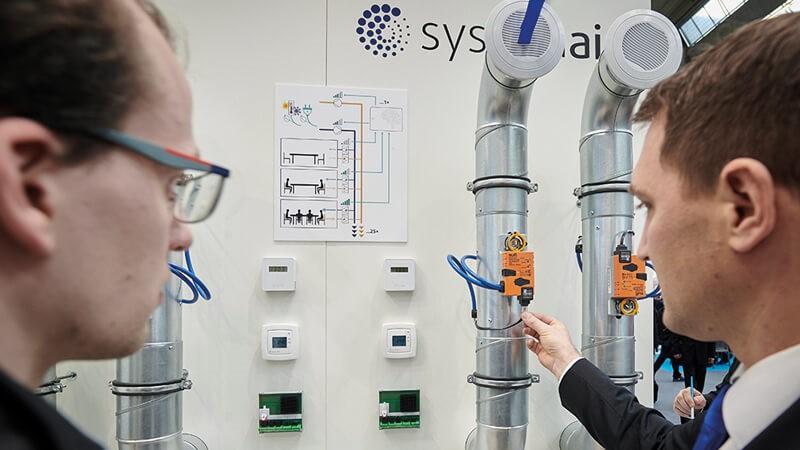 Ein Mitarbeiter von Systemair und ein Messebesucher mit Efficient Ventilation Control, eine Regelung zur digitalen Gebäudelüftung von Systemair.