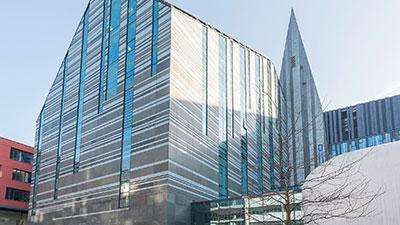 Eingangsfassade der neuen Universitätskirche Leipzig mit zahlreichen Glaselementen.