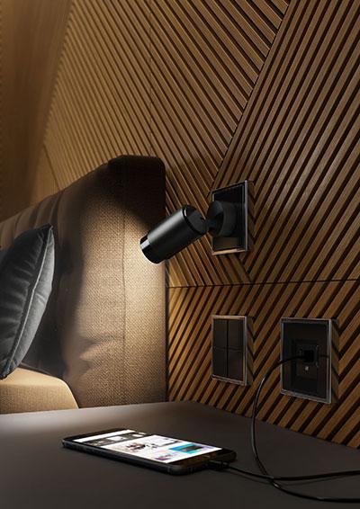Ansicht einer Schlafzimmerwand mit Lichtsteckdose Plug and Light von Insta und Strahler.
