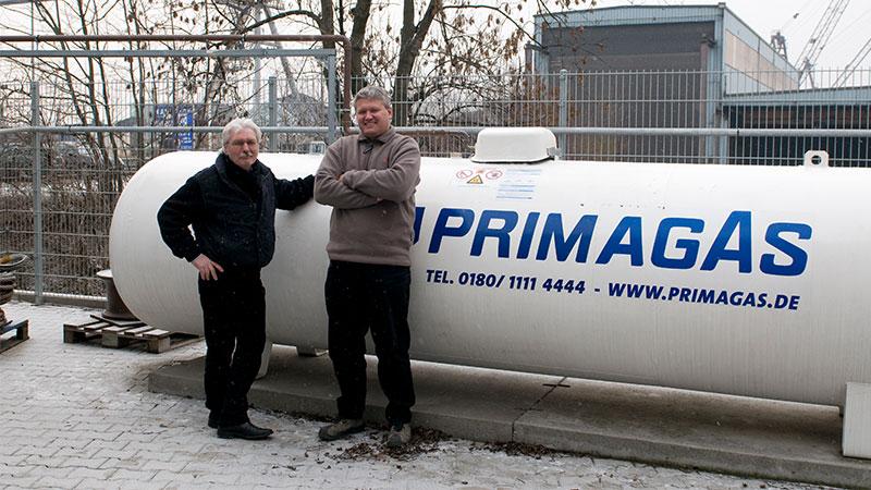 Ein regionaler Kundenberater von PRIMAGAS mit einem Kunden aus der Binnenschifffahrt vor einem Flüssiggas-Tank mit PRIMAGAS Logo.
