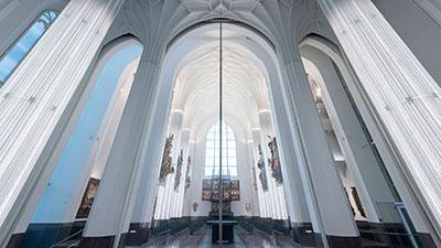 Innenraum der neuen Universitätskirche Leipzig mit raumteilender Glas-Schiebetür.
