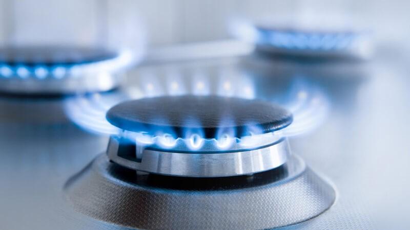Kochstelle eines Gasherdes mit typisch blauen Flammen.