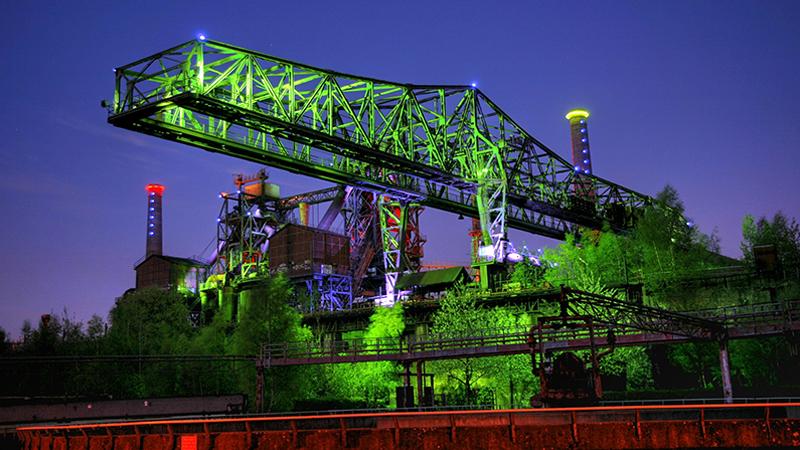 Nächtlich erleuchteter Güterkran im Landschaftspark Duisburg-Nord.