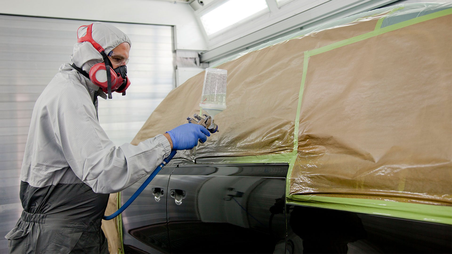 Mann mit Atemschutzmaske und Farbspritzpistole lackiert Auto.