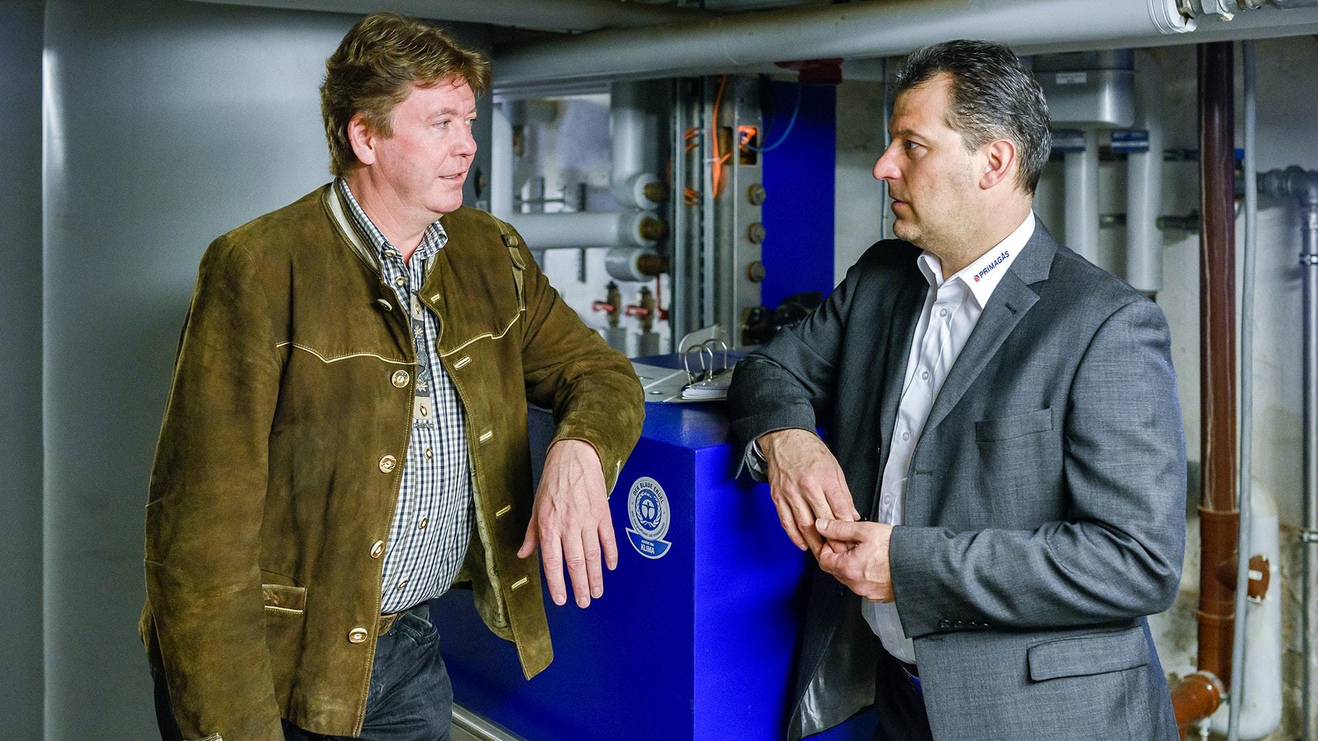Fleischerei-Inhaber Werner Schmid und ein Mitarbeiter von PRIMAGAS vor einem neuen Mini-Blockheizkraftwerk.