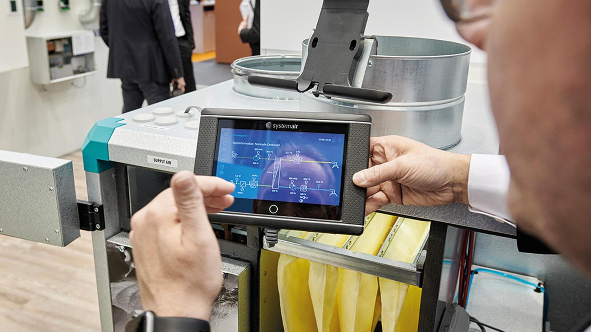 Ein Mitarbeiter der Systemair GmbH mit Bedieneinheit NaviPad, auf dem er Systemair Access – die Regelungslösung für die Geniox- und Topvex-Lüftungsgeräte von Systemair – nutzt.