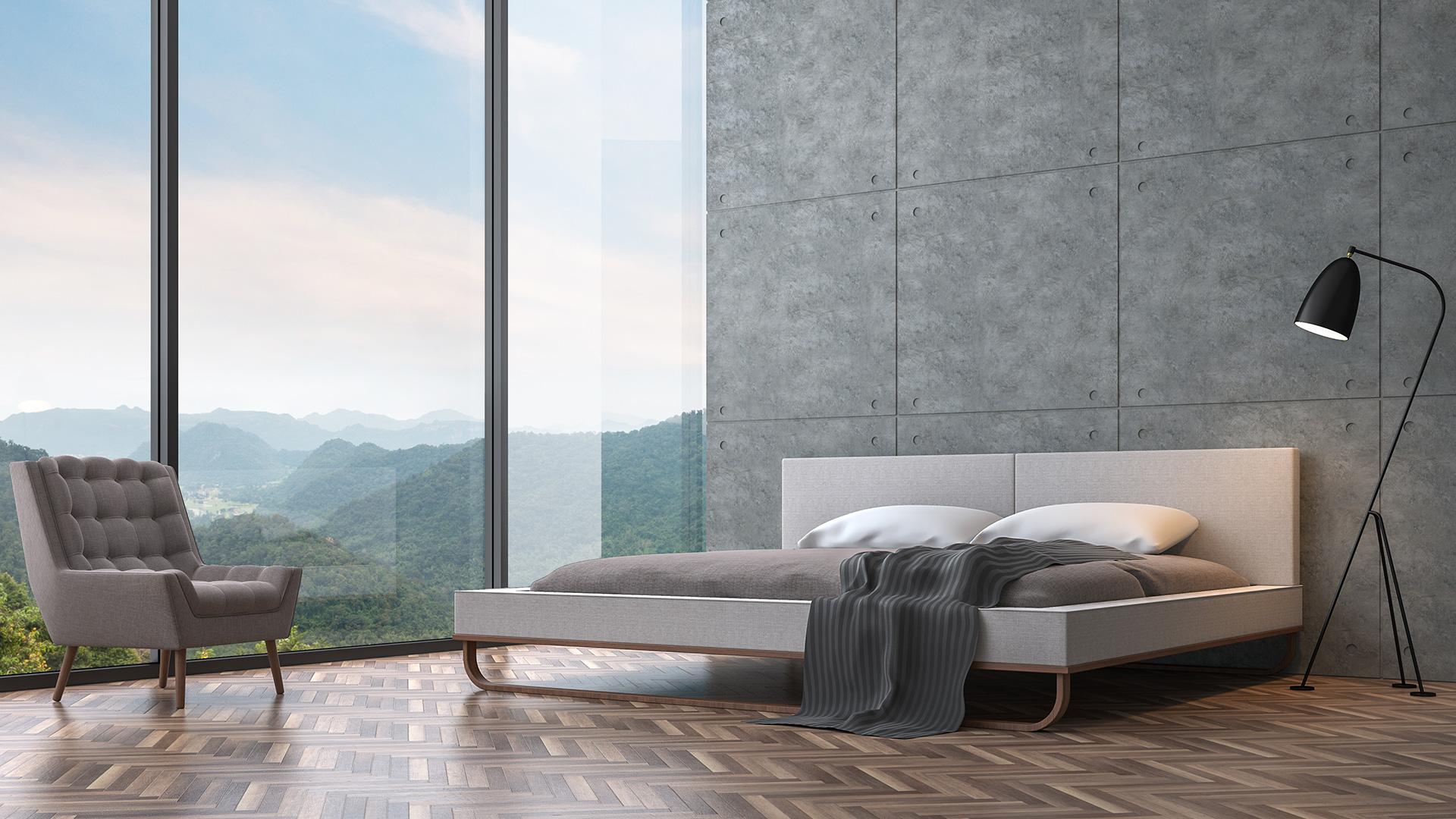 Schlafzimmer eines modernen Wohnhauses mit Sichtbetonwand und Panoramafenster.