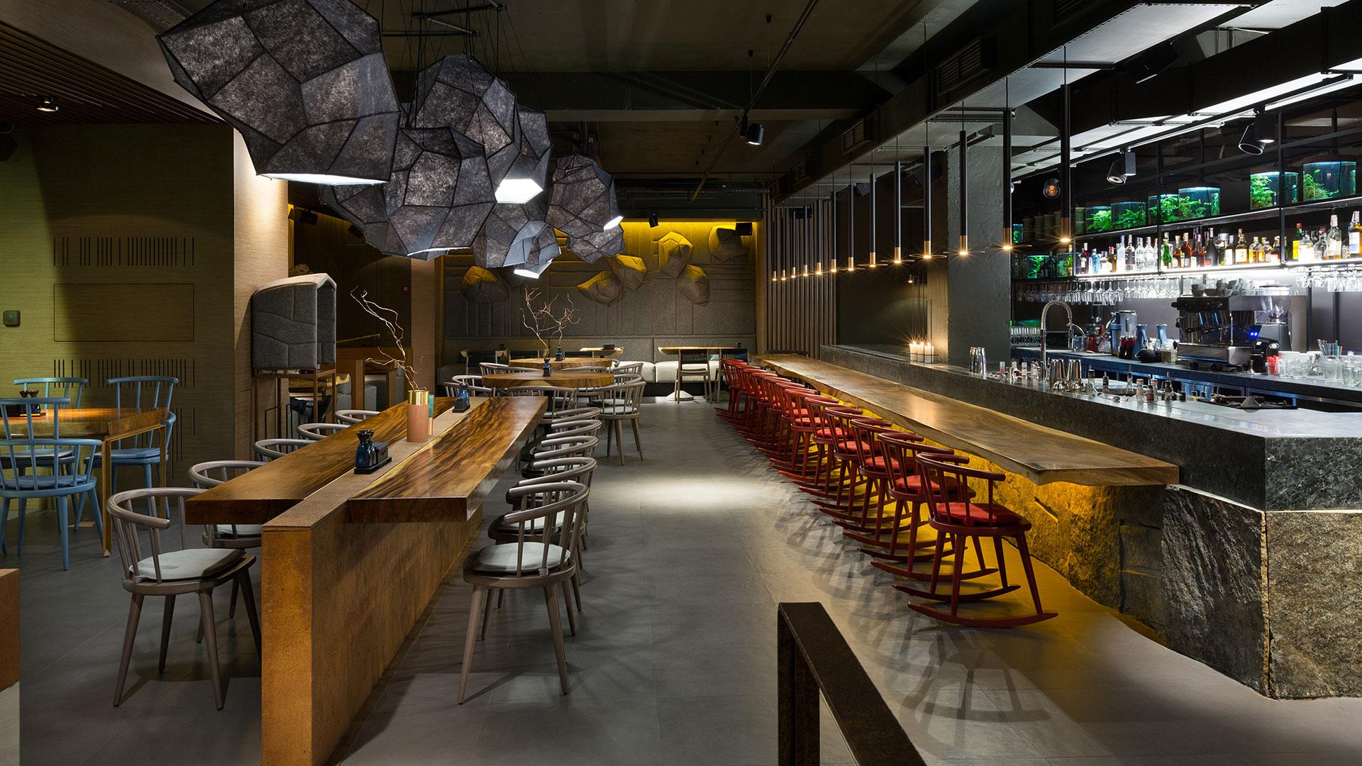 Asiatische Raumgestaltung im Restaurant East Kiew mit Tischplatten aus Palmenholz, Lampen in Form von Steinen und Wandflächen aus rostigem Metall.