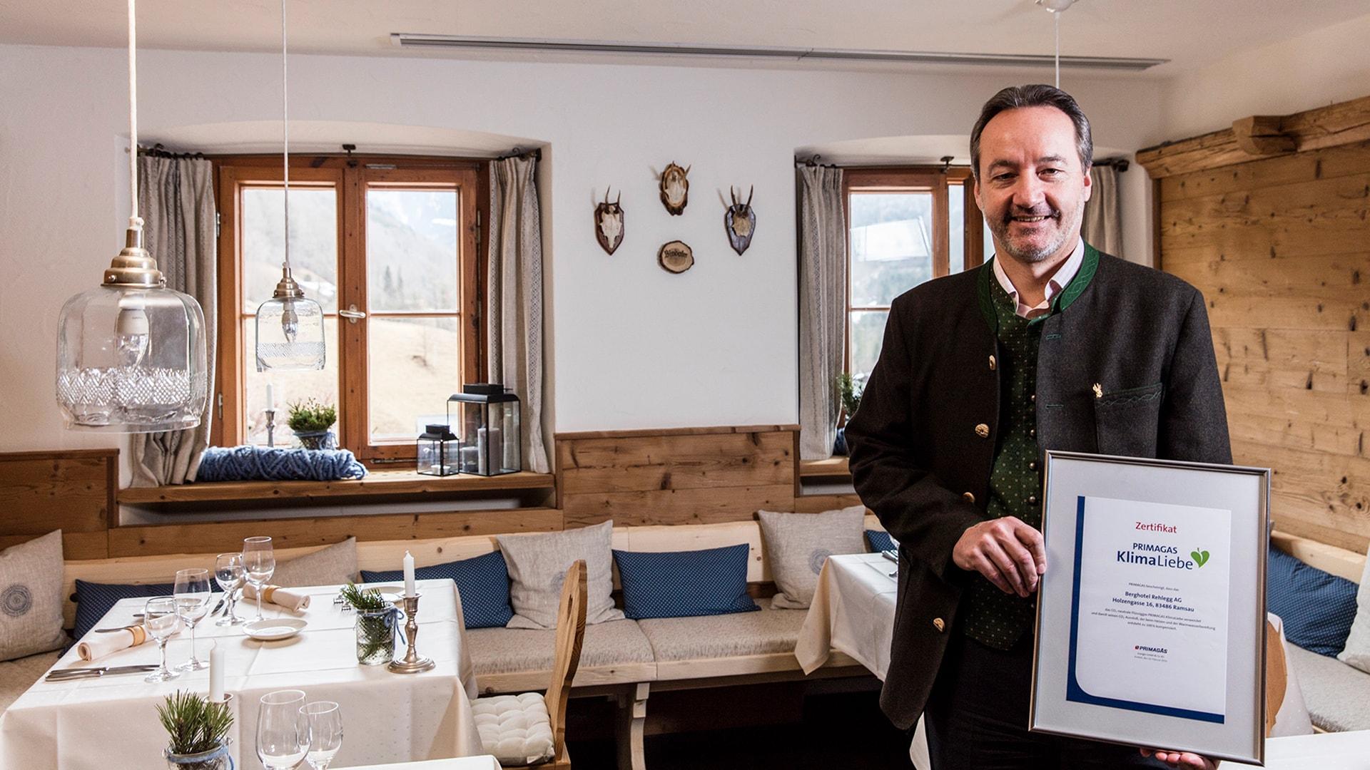 Johannes Lichtmannegger im Speisesaal seines Berghotels Rehlegg mit KlimaLiebe-Zertifikat von PRIMAGAS.