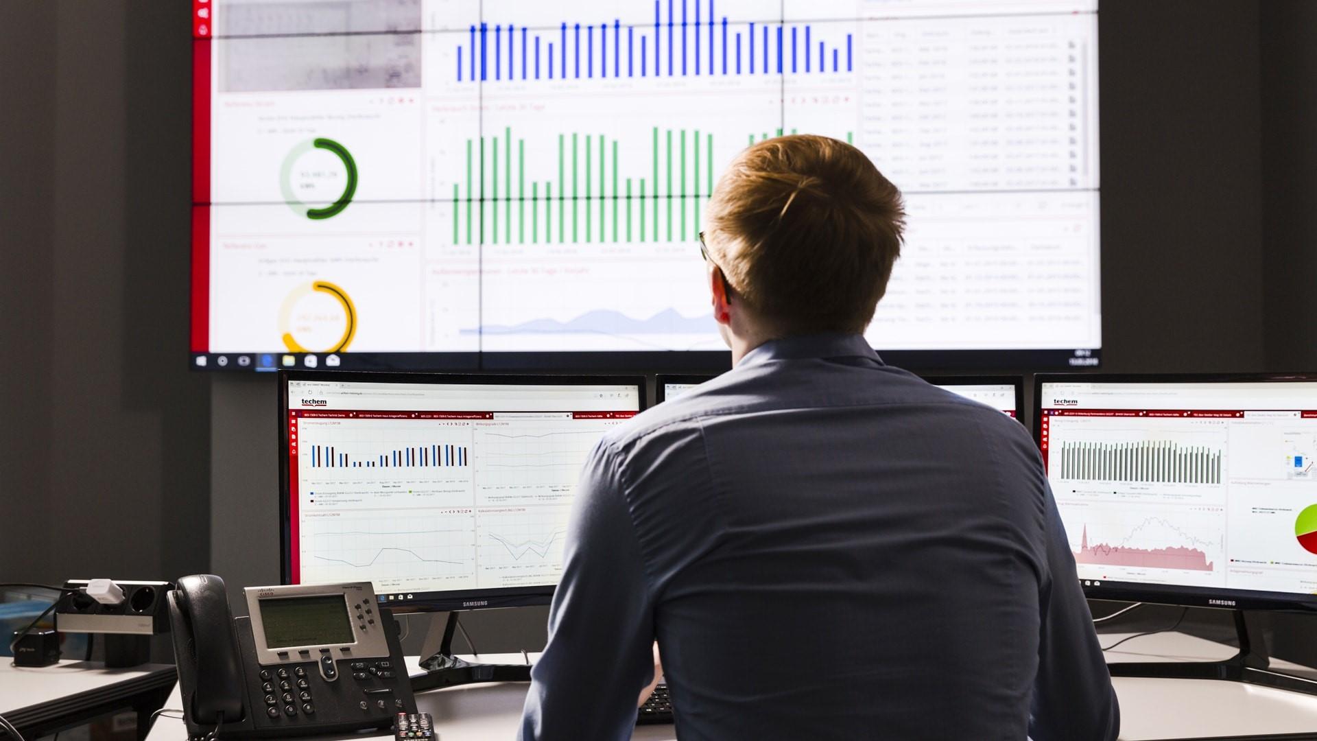 Mann überwacht Daten über ein digitales Dashboard.