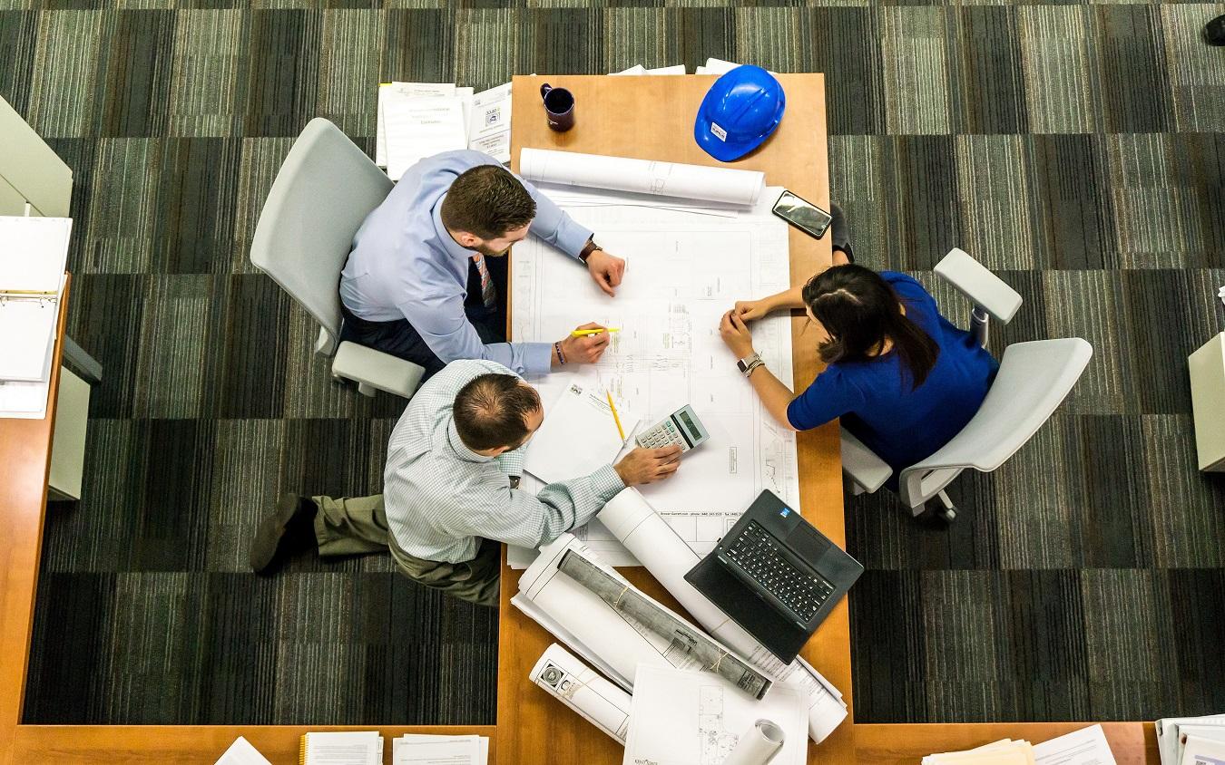 Symbolbild: Architektenteam, das an einer Skizze (Gebäudeplanung) arbeitet.