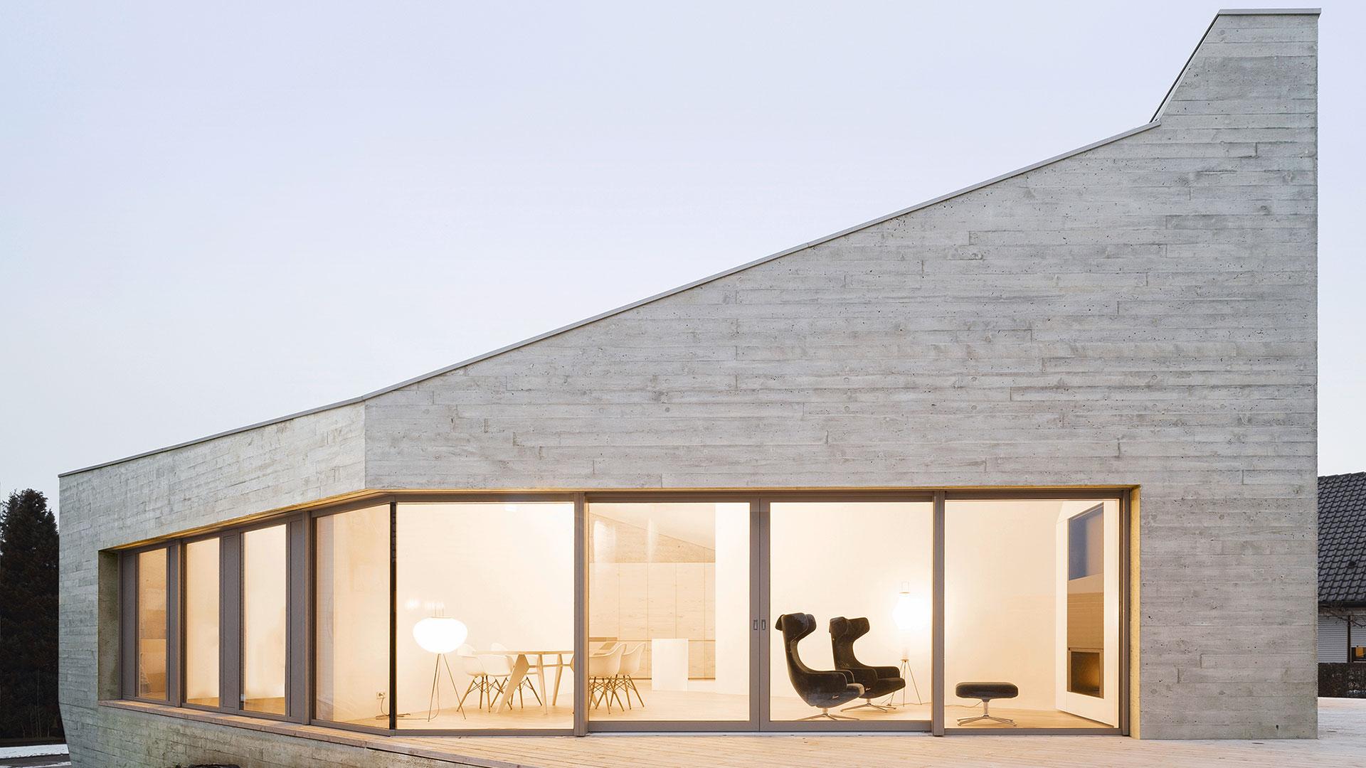Wohngebäude in monolithischer Bauweise, Ansicht seiner großflächigen Terrasse und Fensterfront mit Blick ins Innere.