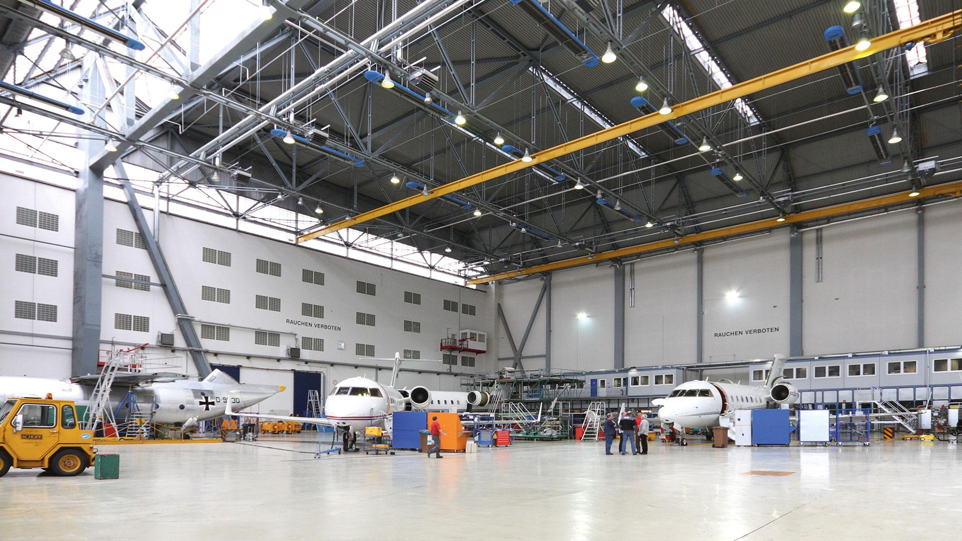 Hangar mit Flugzeugen, Gabelstapler, Personal.