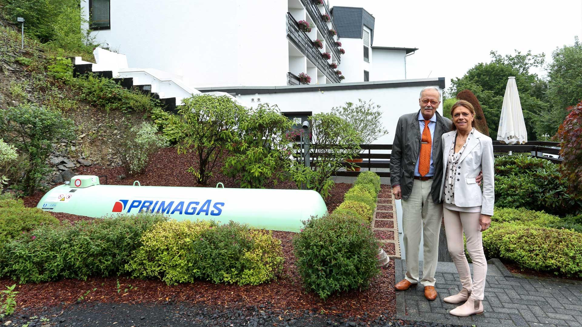 Petra und Christoph Vömel vor halb erdgedecktem Flüssiggas-Tank mit PRIMAGAS Logo, im Hintergrund das Pflegeheim Haus Tannenhof.