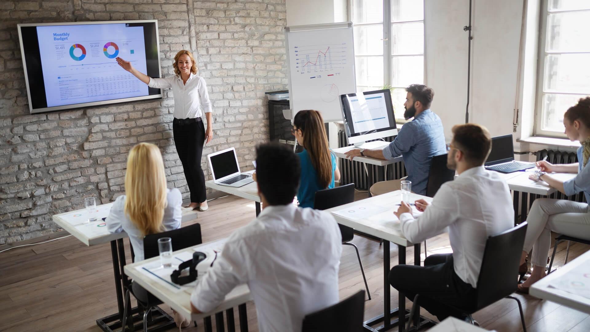Seminarleiterin an großem Bildschirm vor TGA-Fachplanern in Weiterbildung.